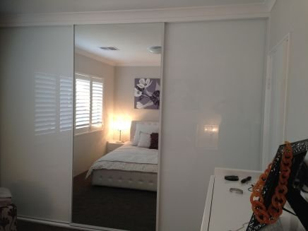 sliding mirrored wardrobe reflecting white bed