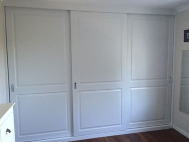 white paneled sliding wardrobe with silver handles
