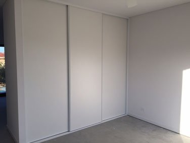 corner of room with white sliding wardrobe and wall