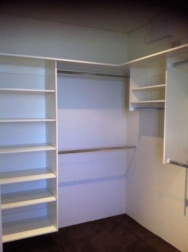 corner of white shelved and silver rod walk in wardrobe