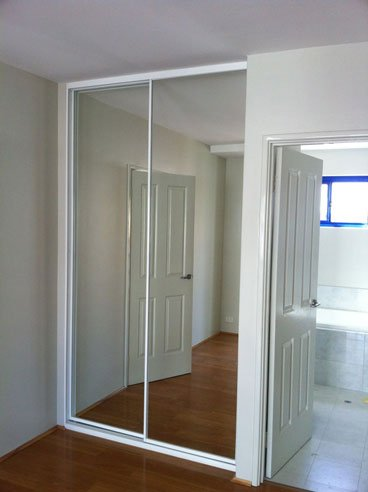 built in mirrored sliding door with white frames next to bathroom door