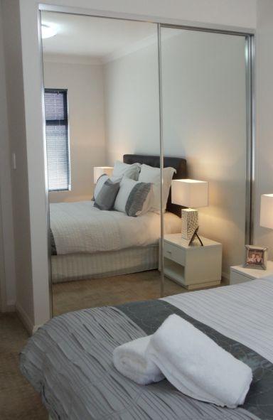 mirrored 2 panel sliding wardrobe reflecting white bed