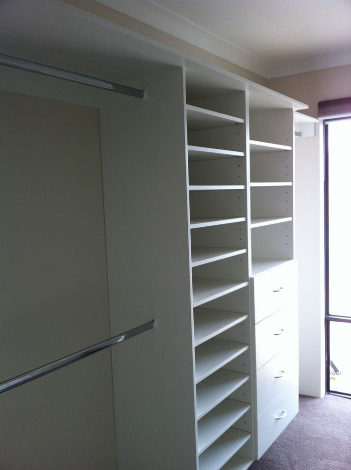 second view of walk in wardrobe with white shelves