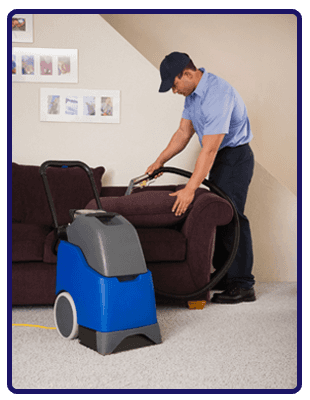Man cleaning a sofa with a blue and grey upholstery cleaner