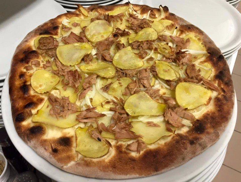 una pizza con salsiccia, formaggio e rucola