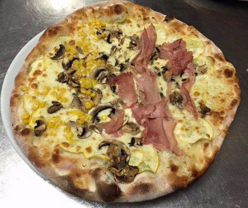 una pizza bianca con funghi, carne e mais