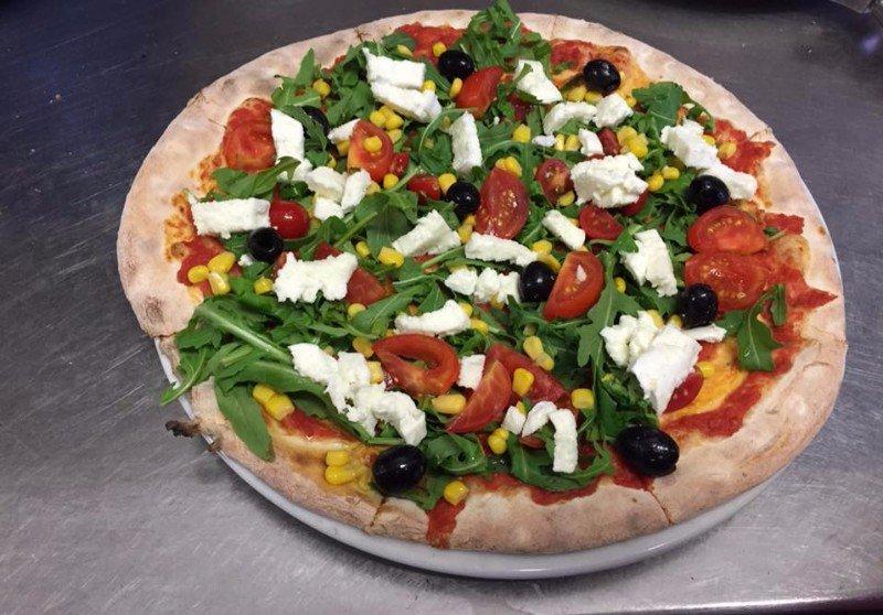 una pizza con mais, pomodori freschi e mozzarella