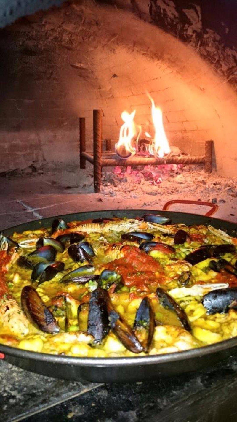 un forno a legna e accanto una pentola con un piatto a base di pesce