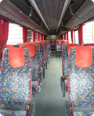 The inside of a Lords coach with multicoloured seats