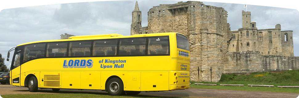 yellow coach in front of a stone building