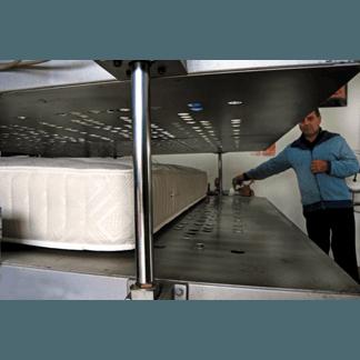uomo con macchina per cucire del materasso del bordo automatico