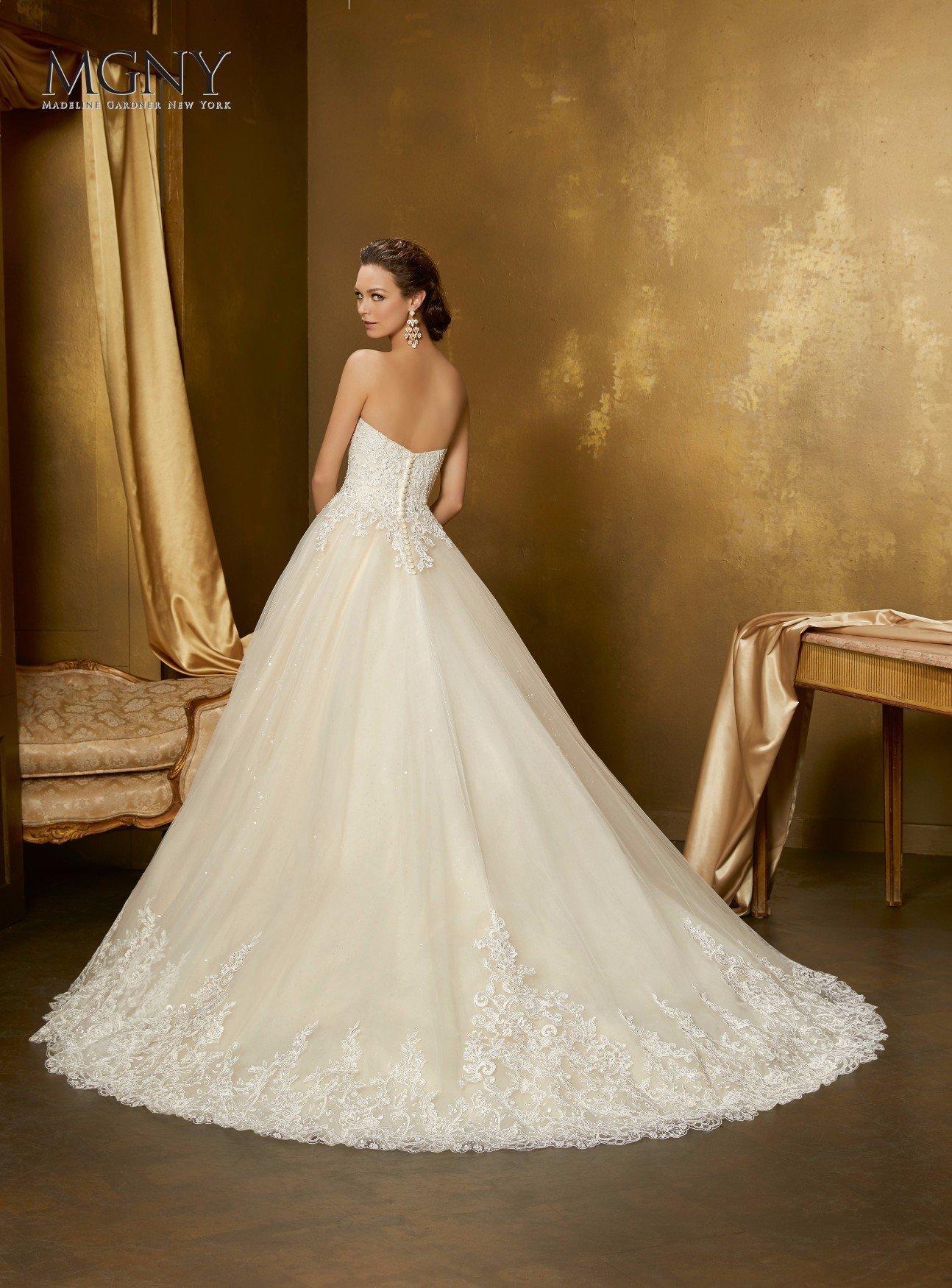 Sposa mostra di spalle il suo abito bianco
