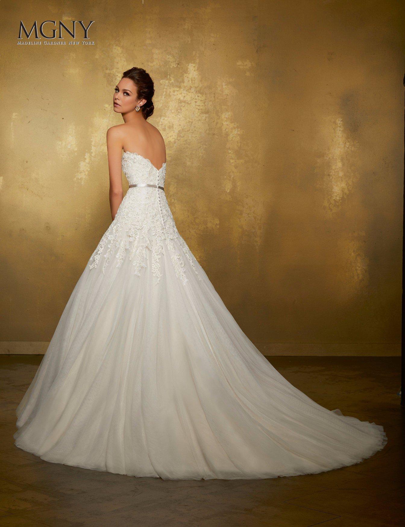 Donna bruna che si prova un abito da sposa bianco