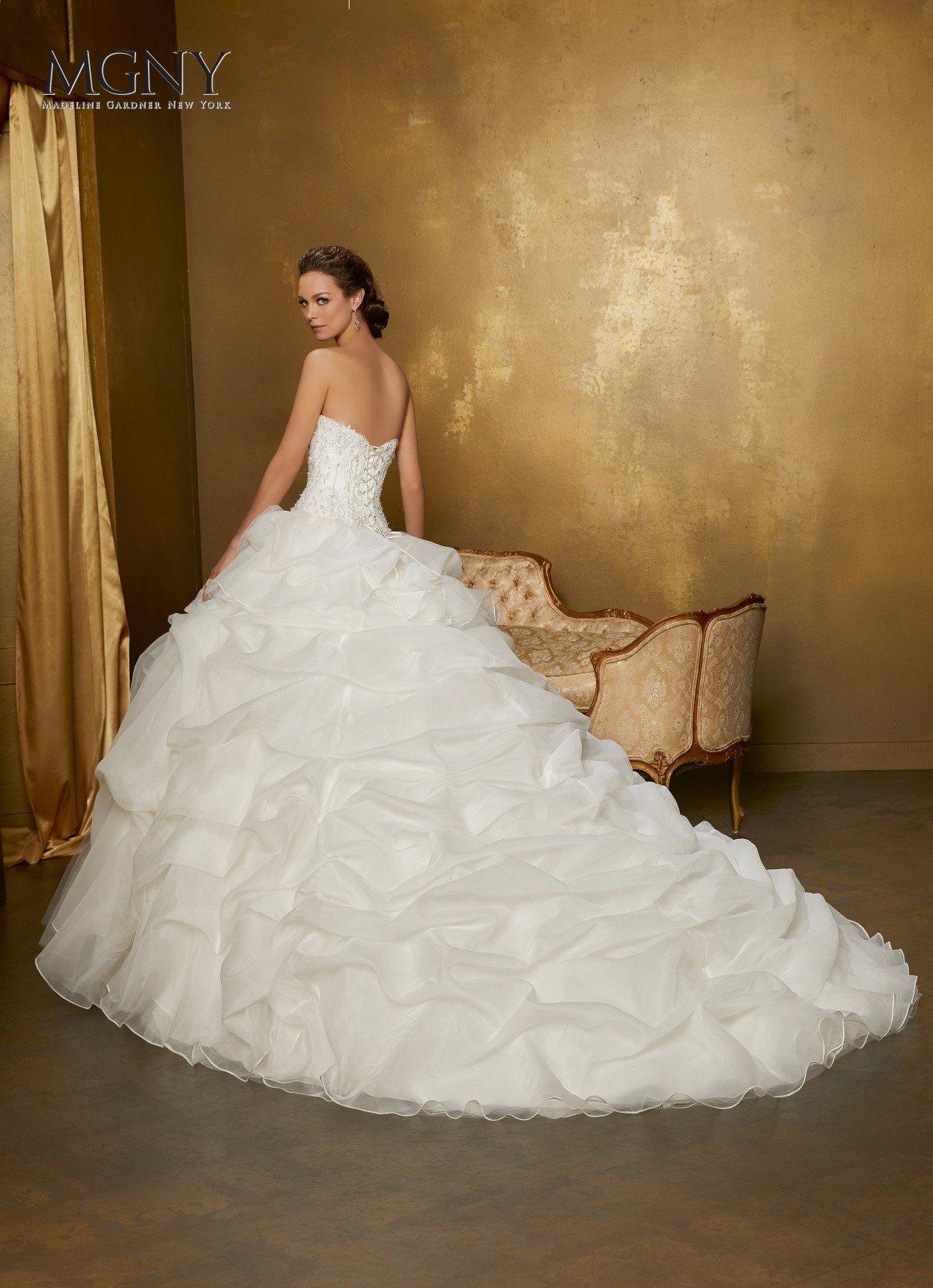 Una donna mostra con soddisfazione il suo abito da sposa