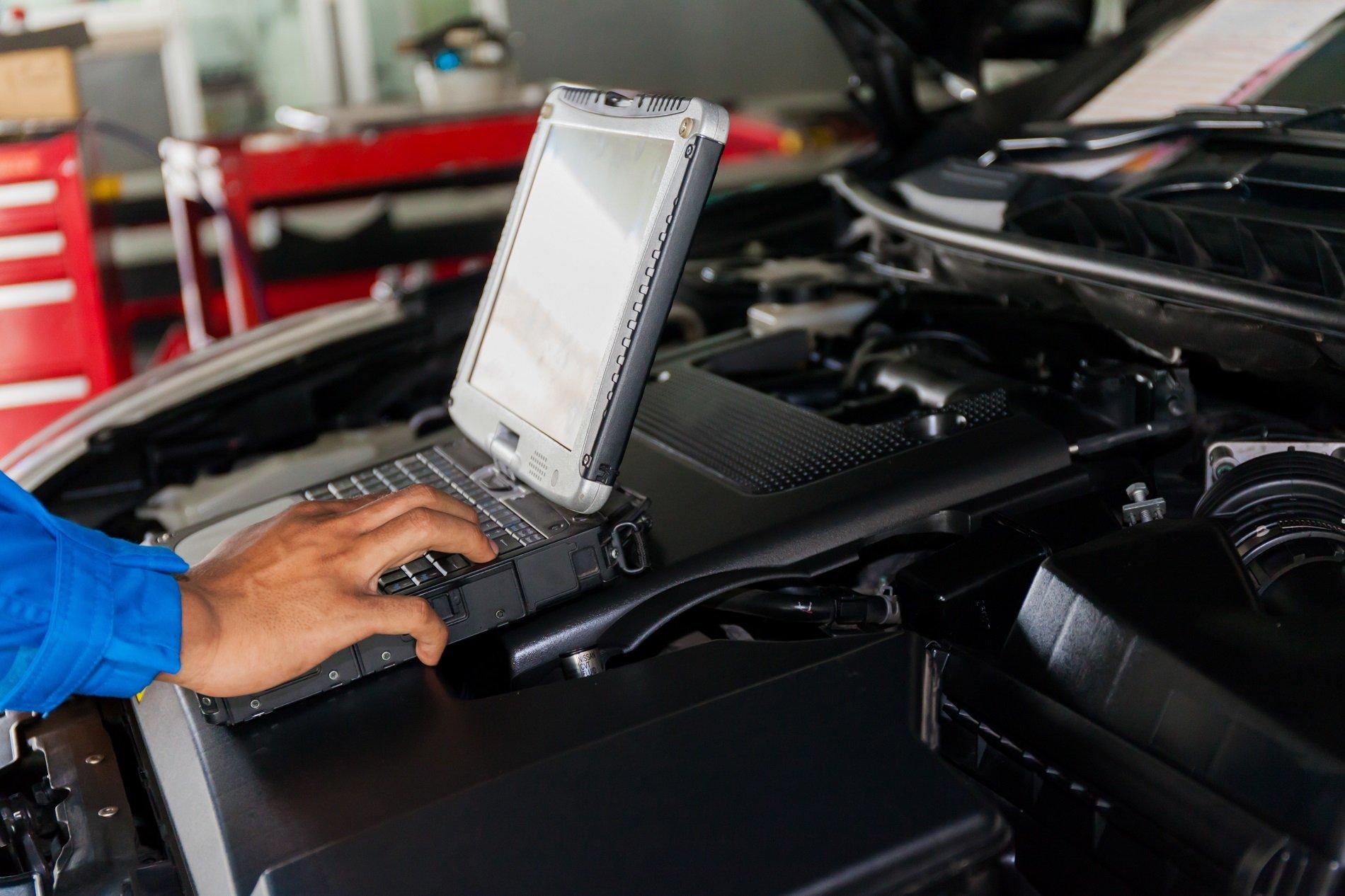 una mano che usa un computer portatile appoggiato sul motore di una vettura