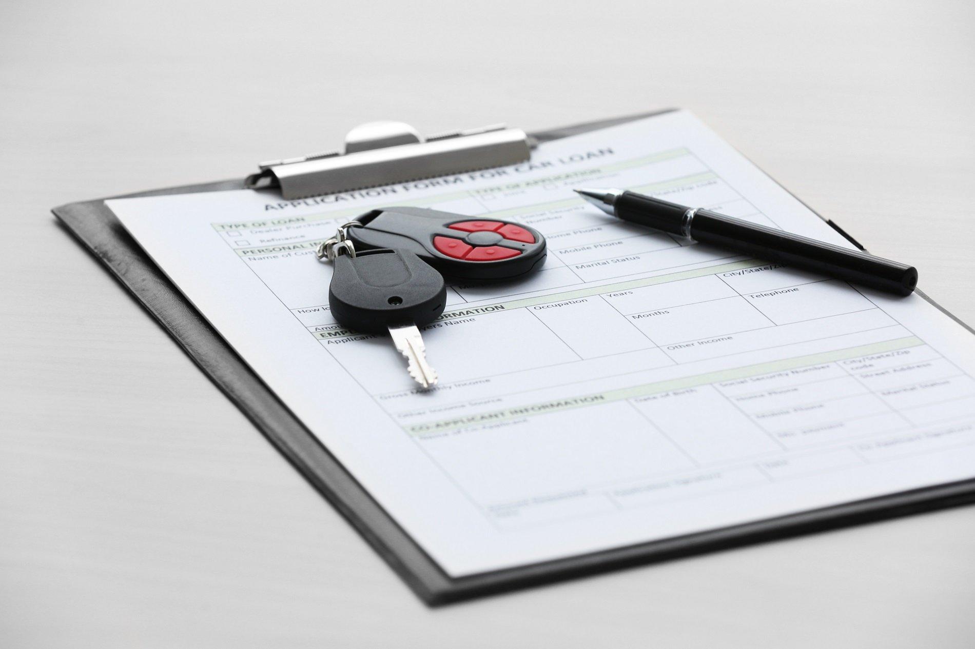 dei documenti e sopra un mazzo di chiavi di una macchina e una penna