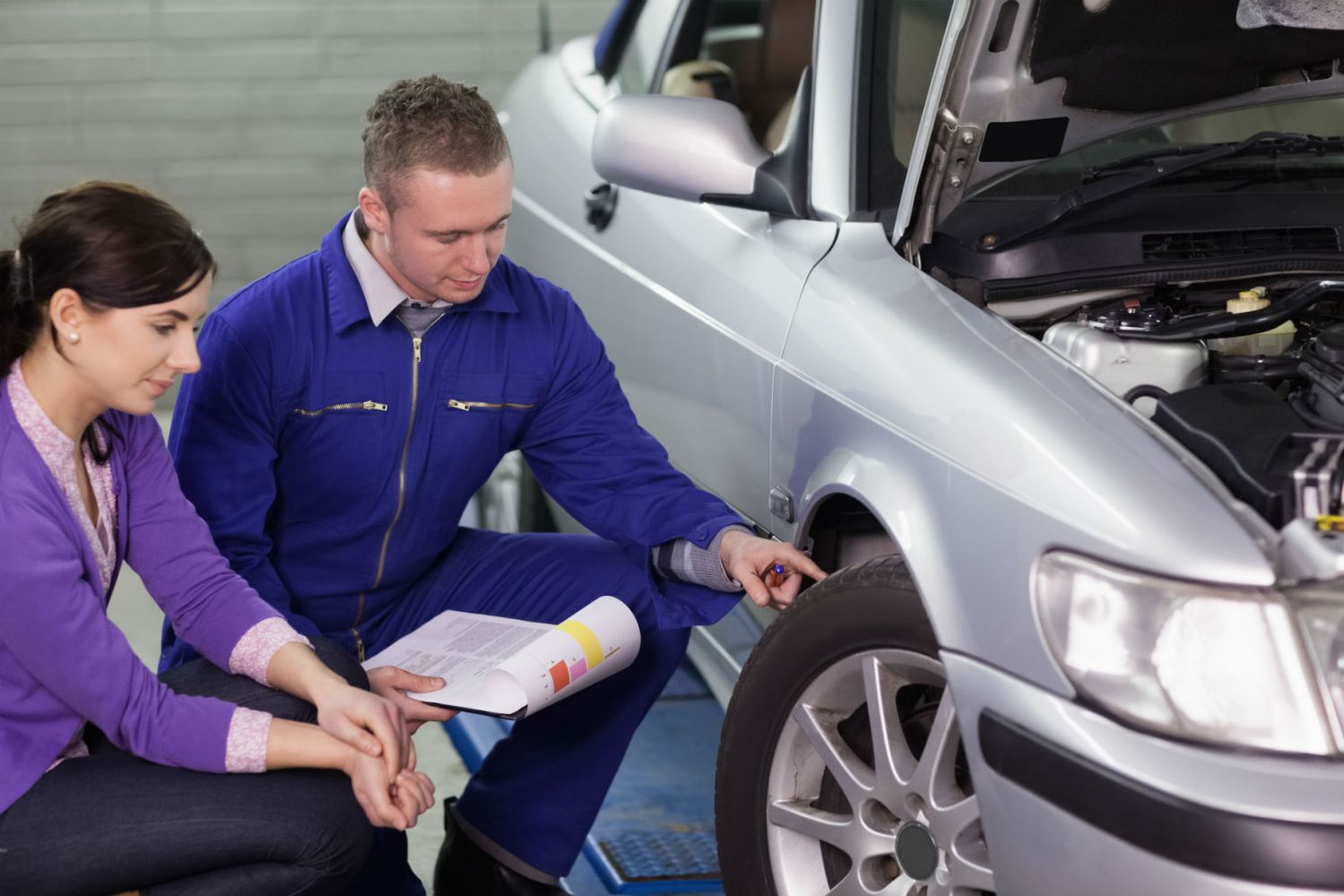 A mechanic explaining wheel alignment issues with a customer in Wentzville, MO