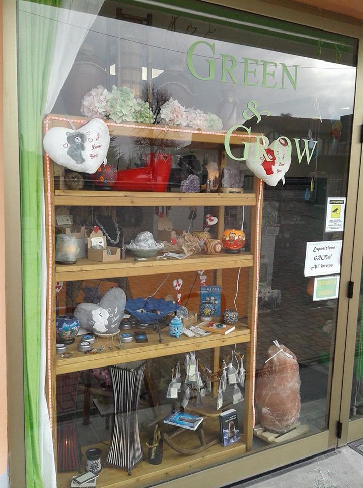 una vetrina vista dall'esterno con scritto green e uno scaffale in legno con degli oggetti