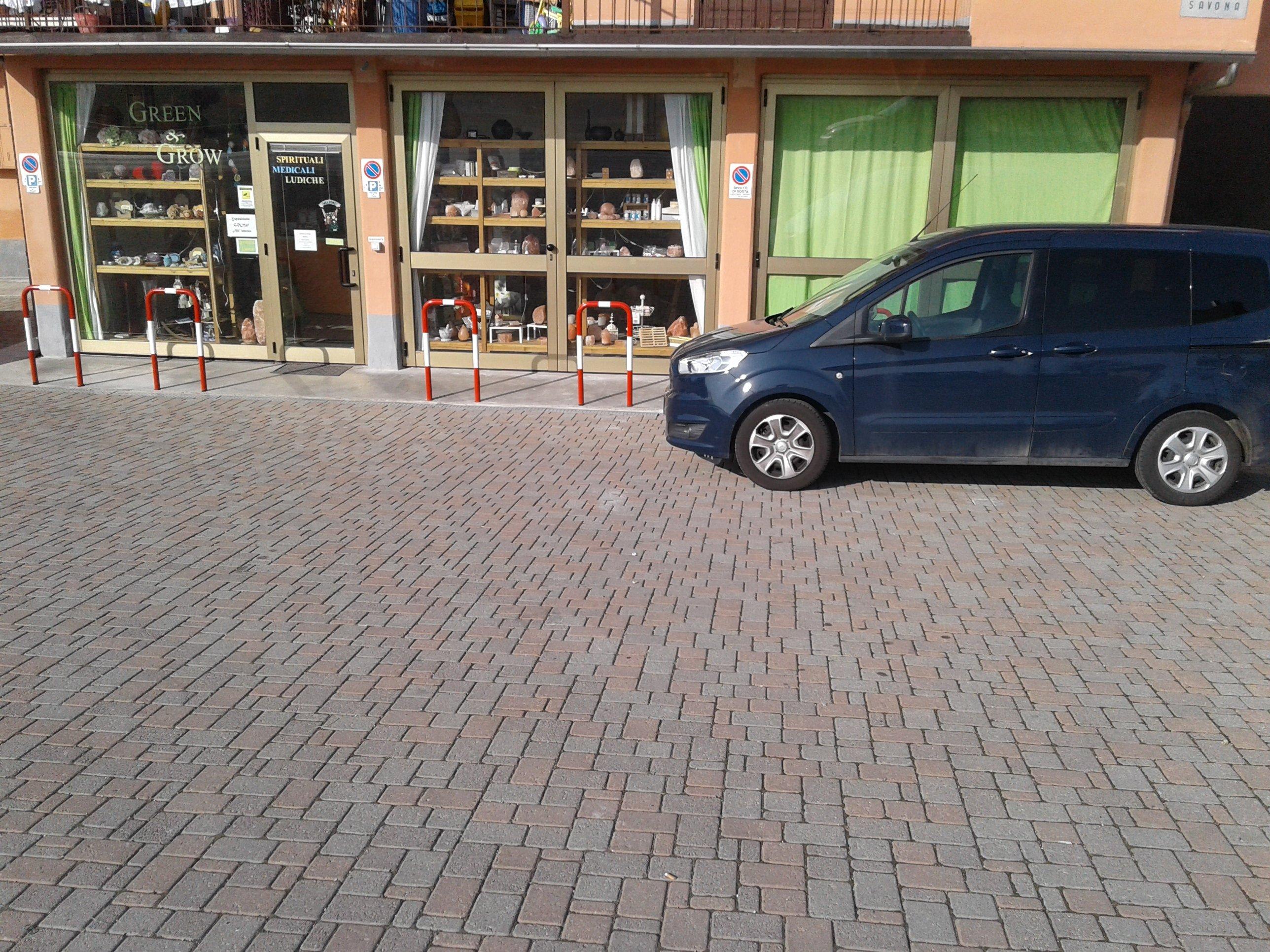 vista di una strada e una macchina parcheggiata fuori dal negozio Green & Grow
