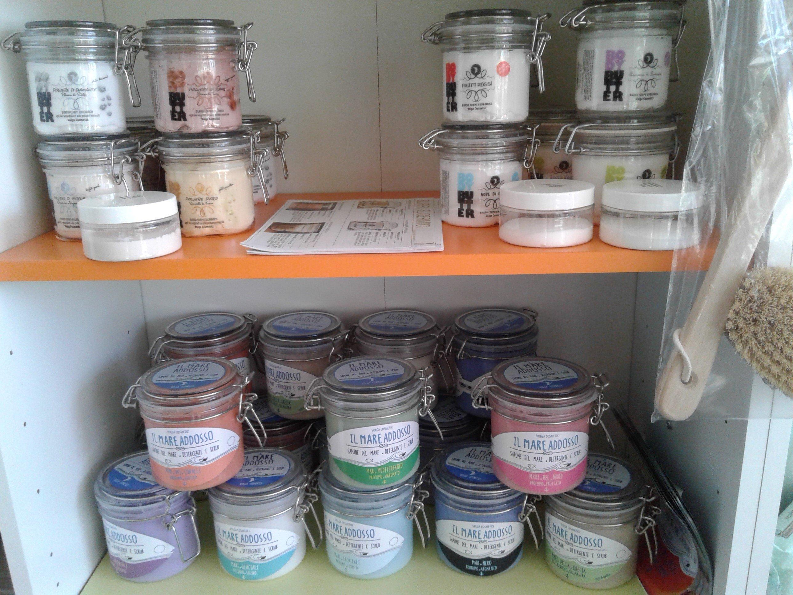 dei barattoli di vetro ermetici in uno scaffale con dentro dei prodotti a gel colorati