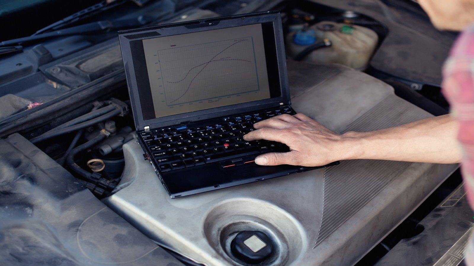 Operaio compiendo la diagnosi computerizzata dell'auto