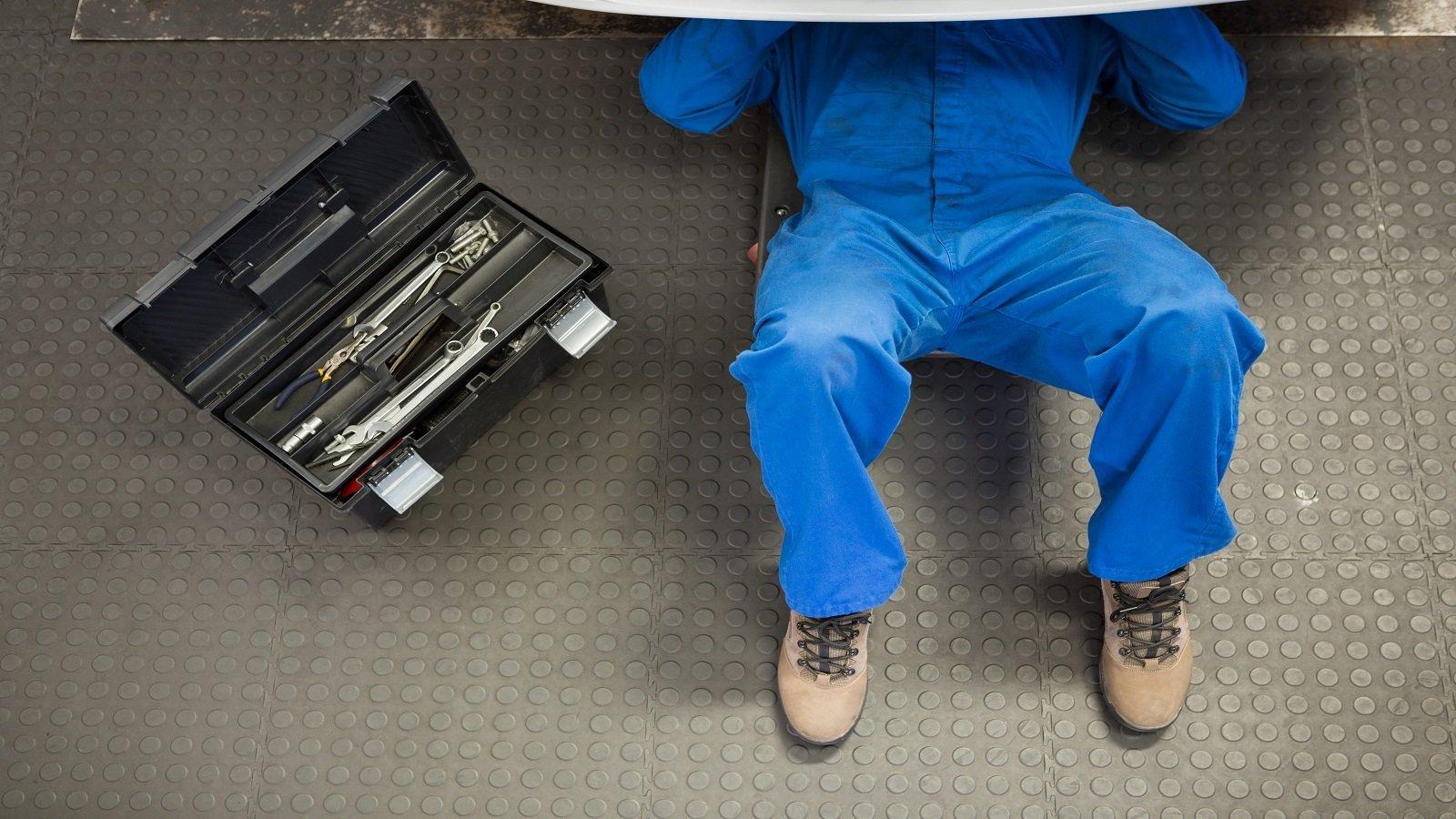 Meccanico lavorando sotto l'automobile, cassetta degli attrezzi al suo fianco
