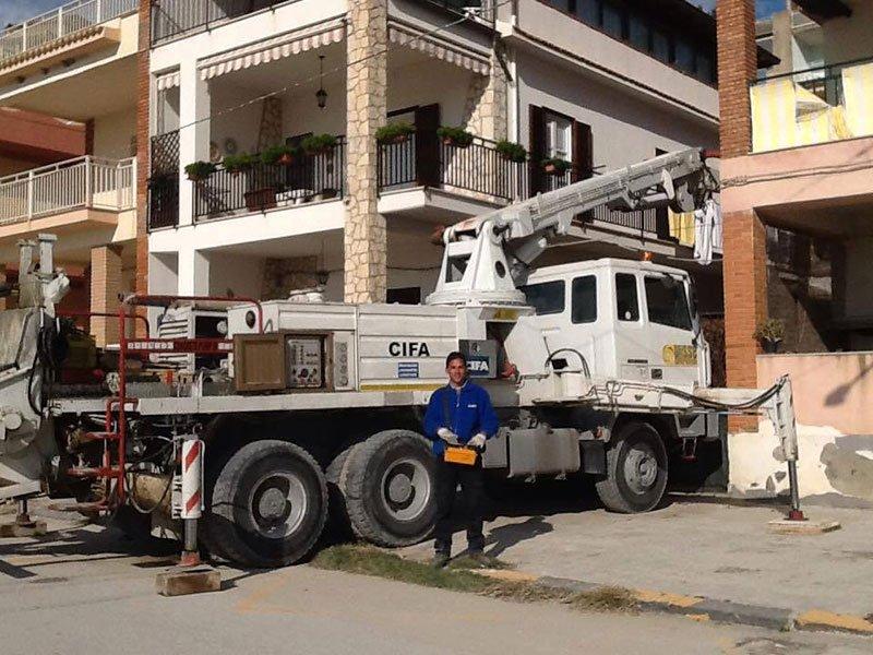 un camion da lavoro vicino a delle case e un uomo davanti