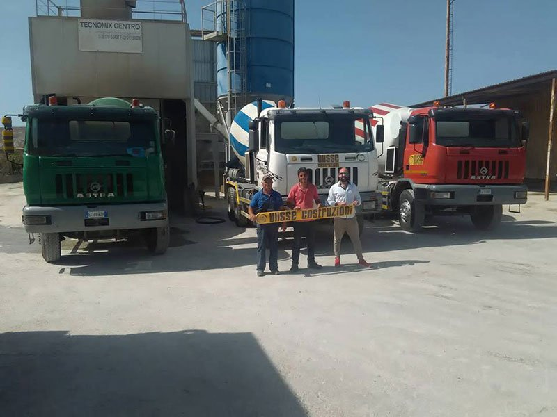 tre persone che tengono uno striscione con scritto Ulisse Costruzioni e dietro dei camion