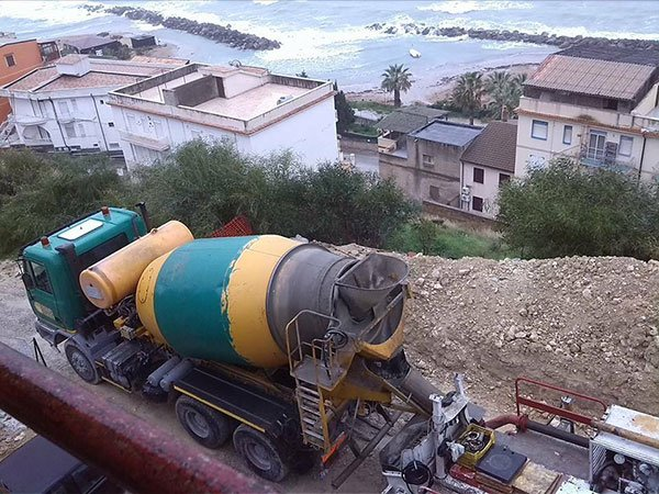una betoniera in un terreno e vista dall'alto di alcune case e del mare