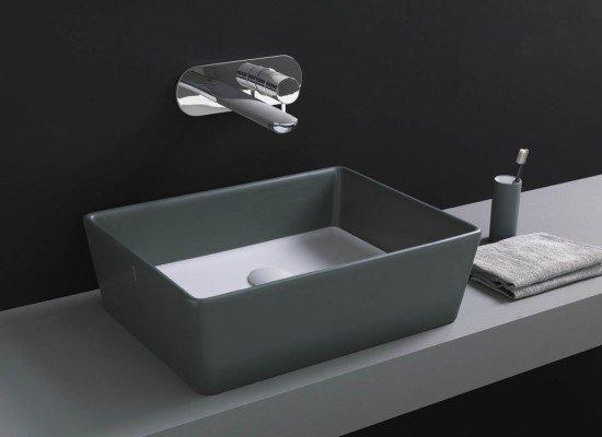 un lavabo rettangolare di color grigio e un rubinetto moderno in acciaio