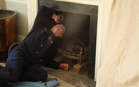 Paul Clarke working on removing build-up from a fireplace flue