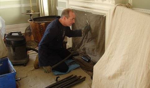 Paul Clarke applying protective dust sheets to a room before starting work