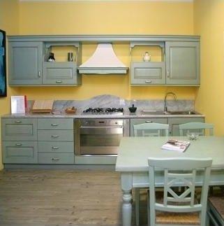 una cucina a blocco di color grigio e un tavolo con delle sedie