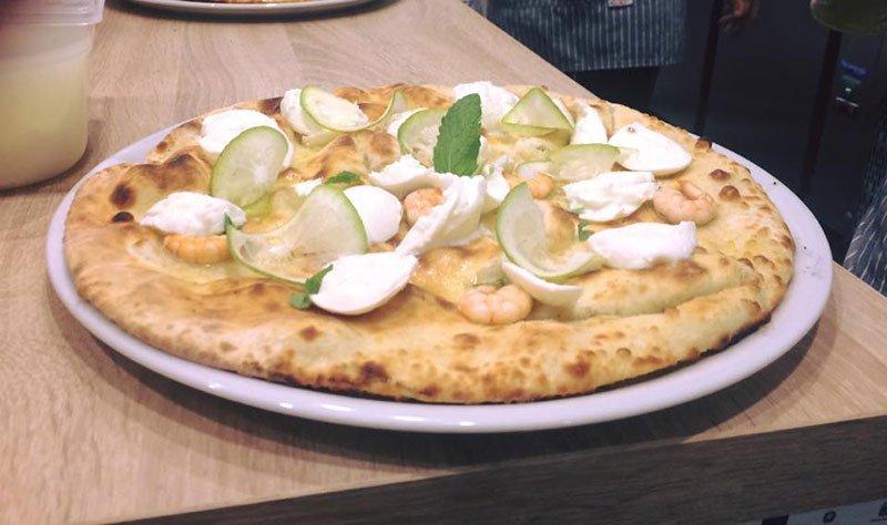 una pizza bianca con gamberi,lime e altro pesce