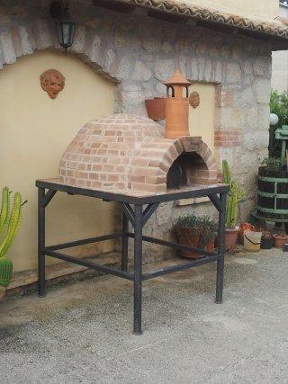un forno a legna con mattoni a vista e un supporto di metallo