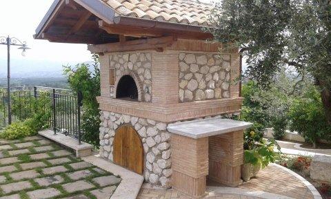 un forno a legna all'esterno con un bancone sul lato e rivestito in pietra