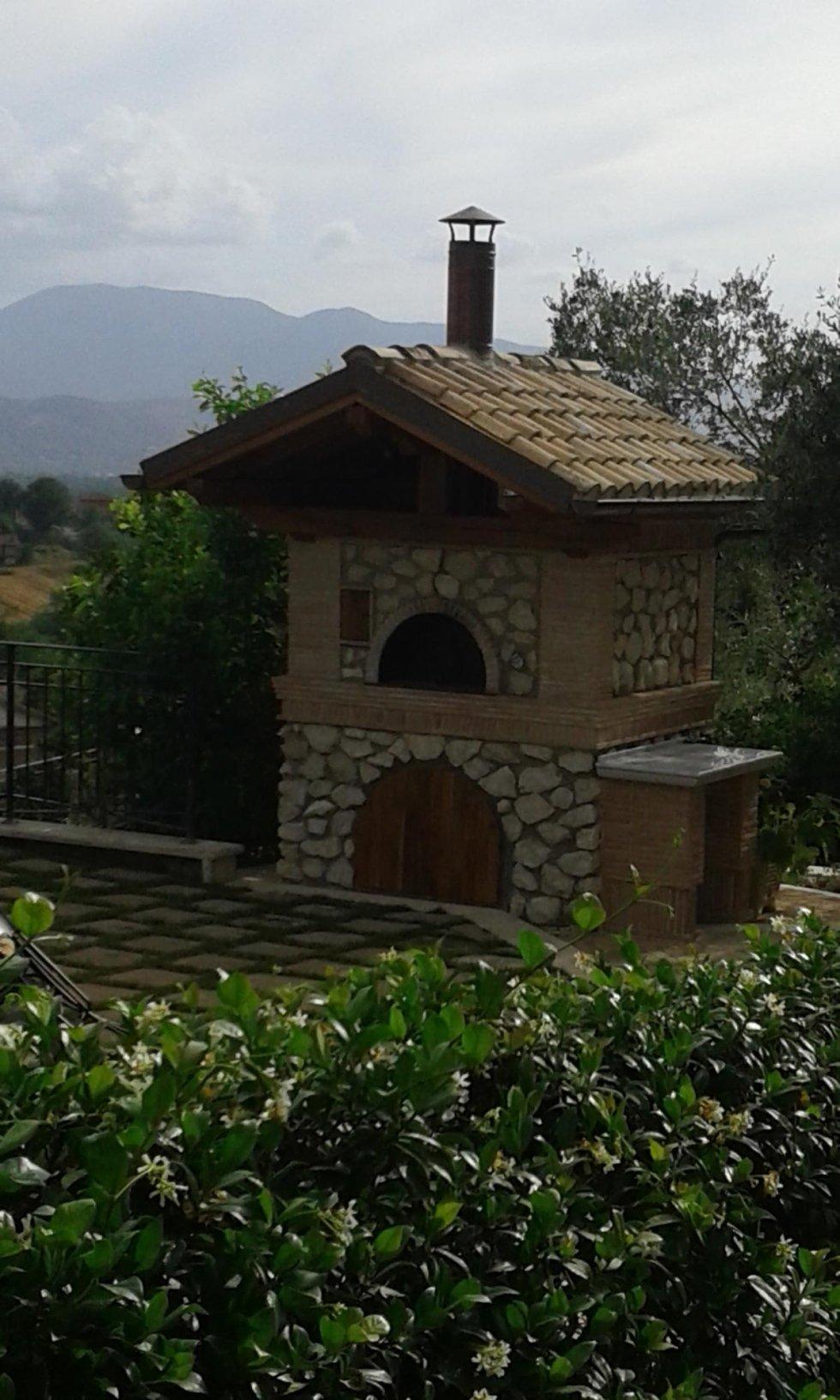 un forno a legna all'esterno e vista delle colline