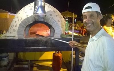 un pizzaiolo in posa con una pala in mano davanti a  un forno