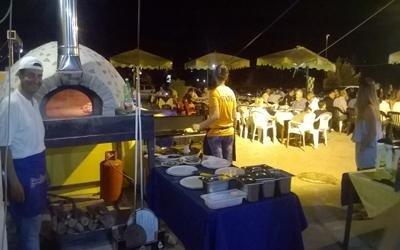 un forno, accanto un bancone e vista delle persone sedute al tavolo
