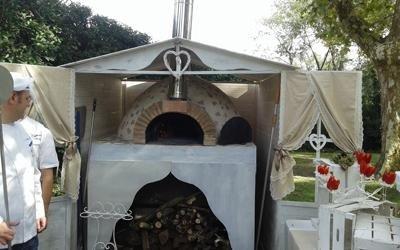 un forno a legna in un prato e un buffet