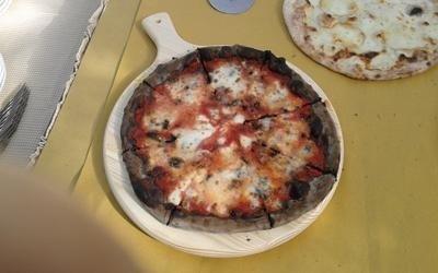 un tagliere con una pizza appena sfornata