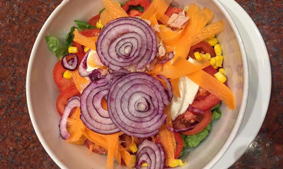 ciotola di insalata mista con carote, cipolle, pomodori, mais e insalata