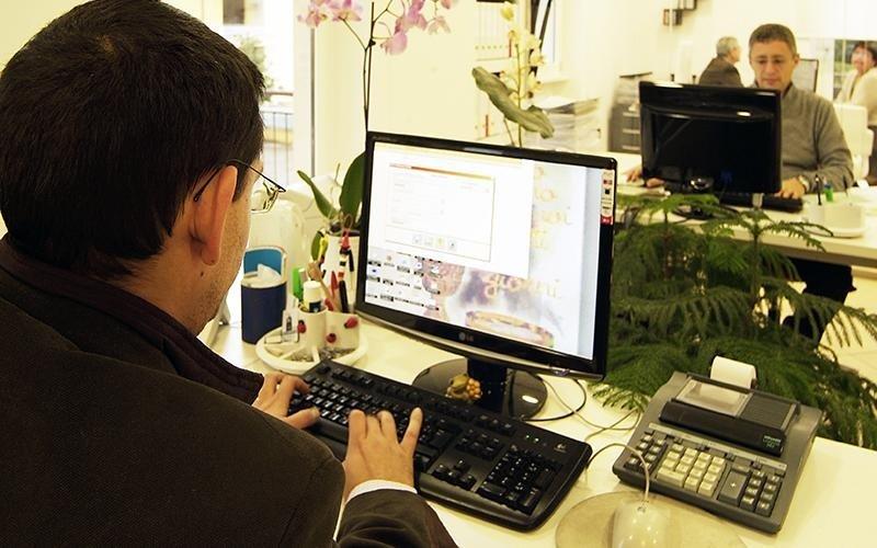 due uomini lavorano in ufficio dietro a delle scrivanie