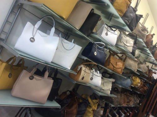 Delle borse di pelle di diversi colori sulle mensole