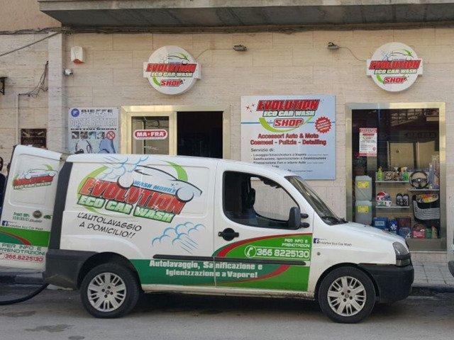 un furgone bianco con scritto Evolution Eco Car Wash di color verde e rosso parcheggiato davanti al negozio
