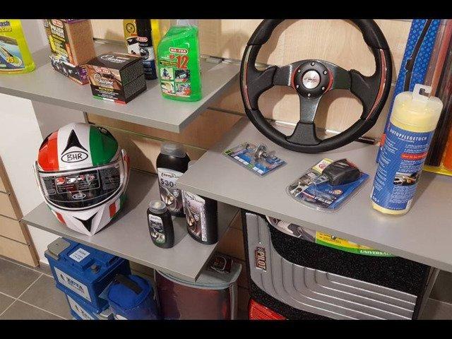 delle mensole grigie con sopra dei prodotti, un casco integrale con visiera, un tappetino e dun coprivolante