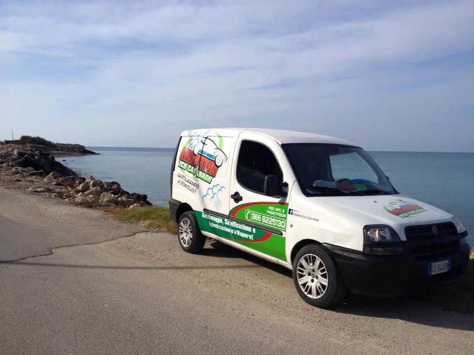 il furgone bianco di Evolution Eco Car Wash parcheggiato su una strada con vista degli scogli e del mare