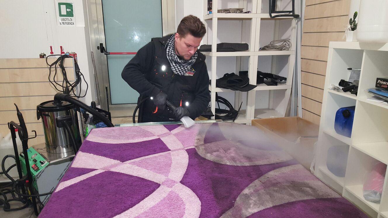 un ragazzo mentre sta pulendo un tappeto viola e rosa con un macchinario