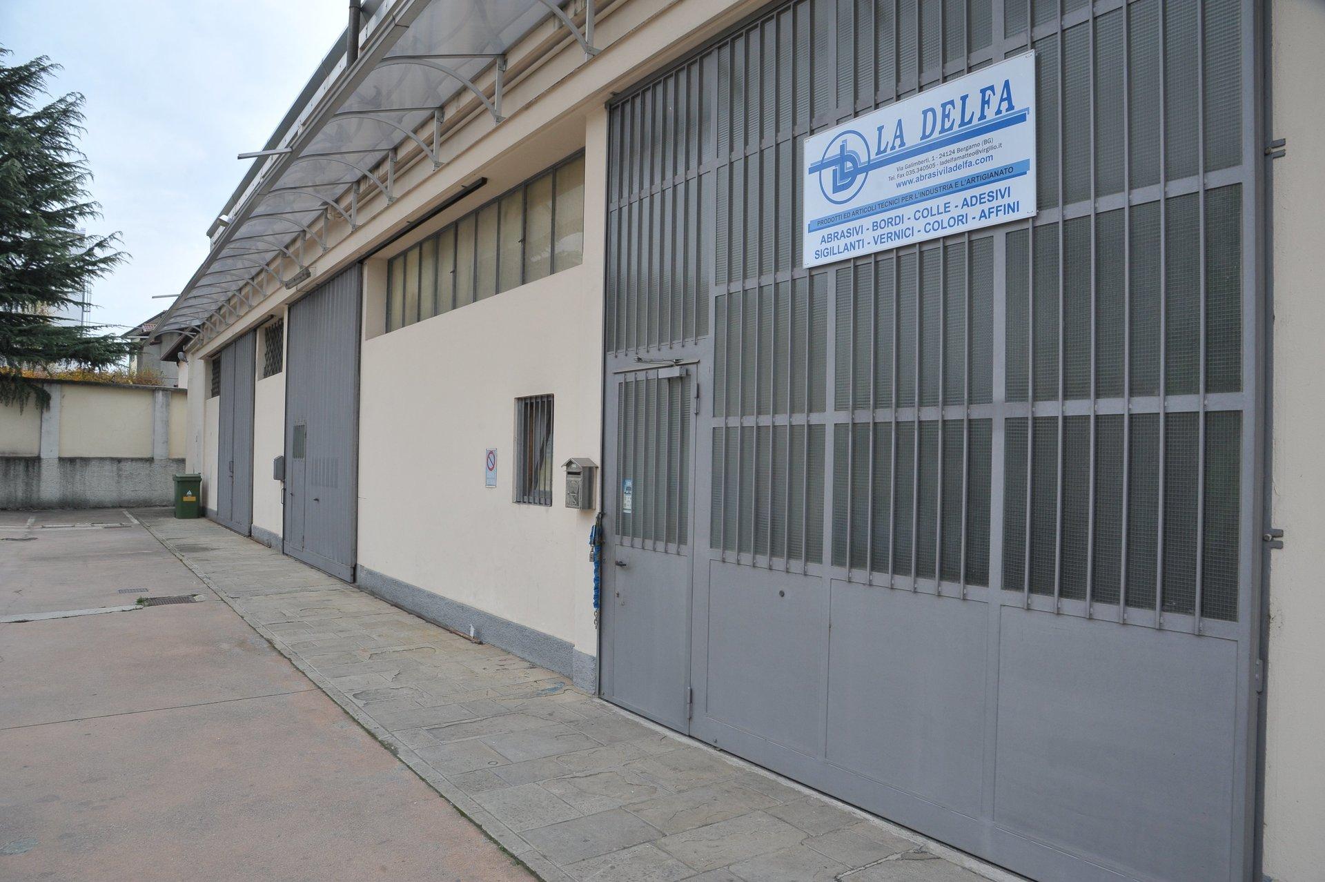 Foto in prospettiva del cancello ferrato d'ingresso al magazzino La Delfa