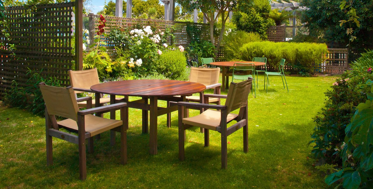 Dining tables and chairs on the lawn of a large garden